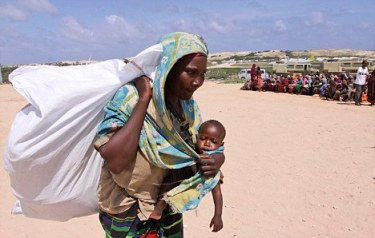 A Somali women carry donated rations of food aid from the UNHCR in Mogadishu , Wednesday. Aug. 31.2011. Somalia's famine refugees are celebrating the Muslim holiday of Eid al-Fitr, which ends a month of fasting, with the food rations distributed by aid agencies for their survival. Eid al-Fitr is traditionally celebrated with grand feasts in which delicacies are in abundance after fasting. (AP Photo/Khalil Senosi)